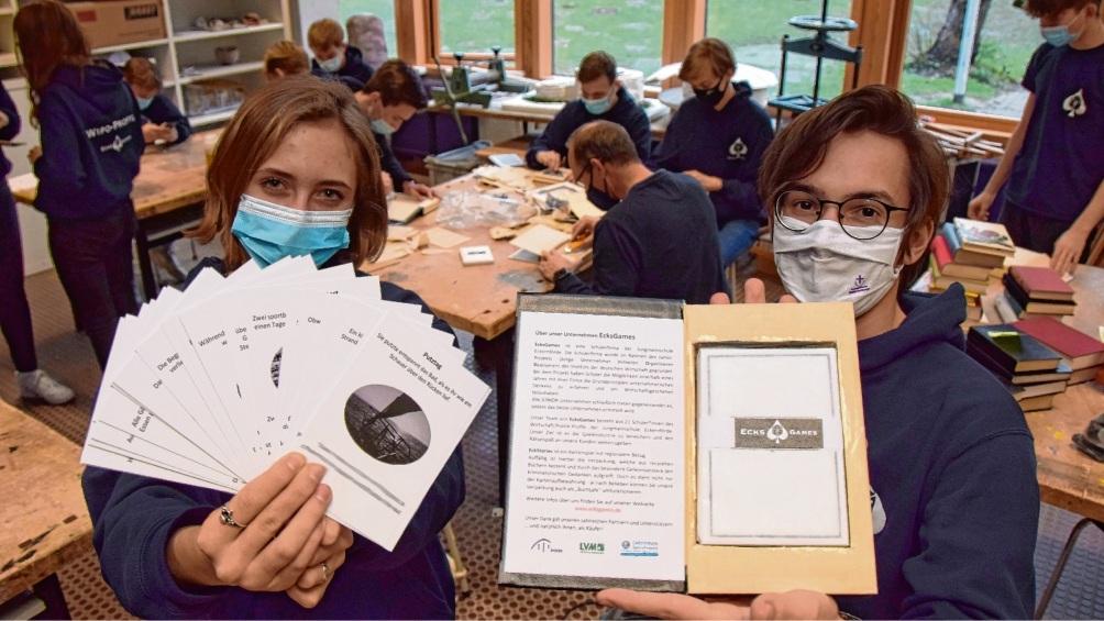 """So sieht das Spiel """"EckStories"""" aus: Bianca Meewes hält die Spielkarten, Tjark Doose präsentiert den Buchsafe, in dem die Karten liegen.  Peters"""