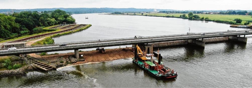 Auch ein Baggerschiff ist im Einsatz: Mit Hochdruck  wird versucht, die Schadensstelle am Damm zu sichern.   Timo Jann