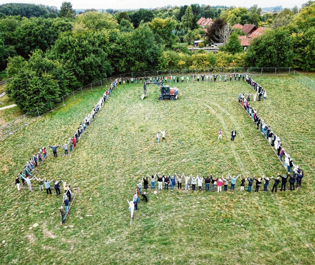 Eine  lange Menschenkette markierte gestern vor dem ersten Spatenstich den Umriss des geplanten Hospizes am Sandkamp. Das Foto wurde von einer Drohne  geschossen. Nico Gladigau