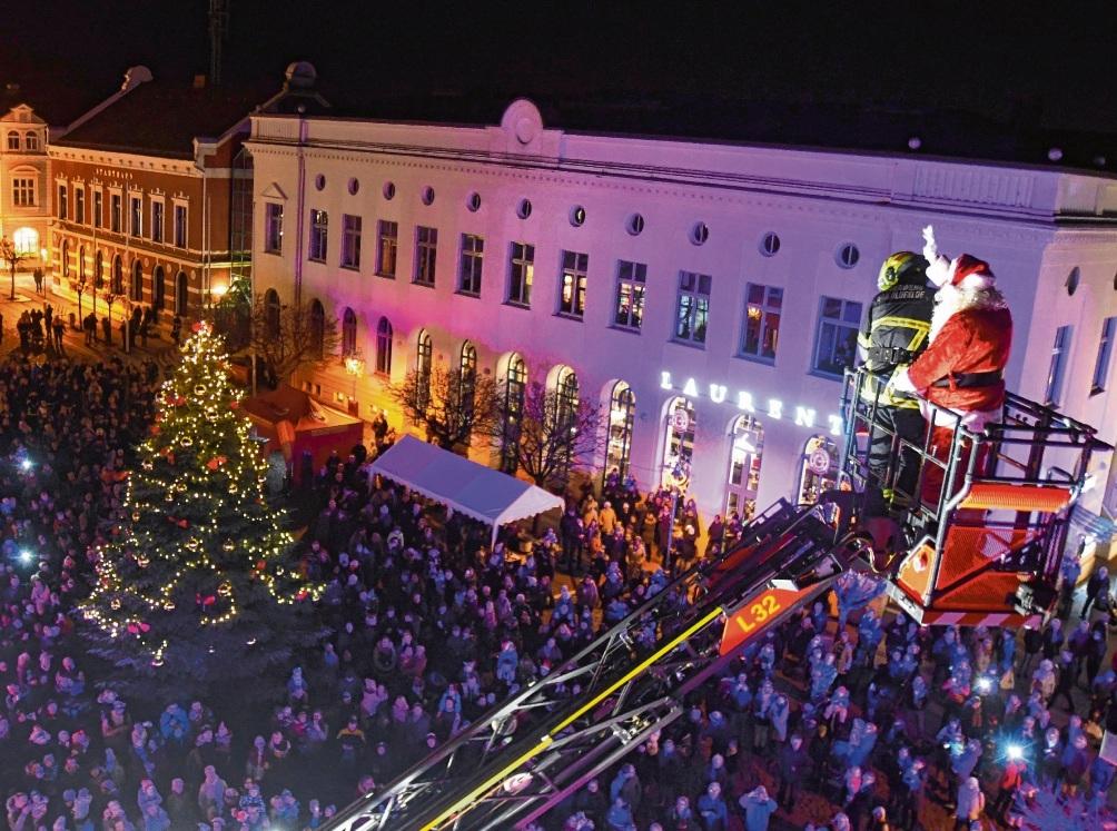 Ho, ho, ho: Der Weihnachtsmann grüßt aus luftiger Höhe. Der Marktplatz ist proppevoll. nie