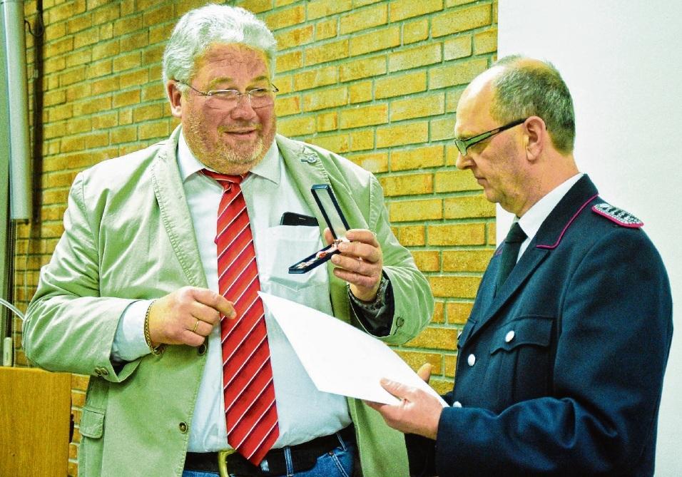 Horst Möller (links) übergibt  als Stellvertreter des Oldesloer Bürgermeisters das Brandschutzehrenzeichen in Gold des Landes Schleswig-Holstein an Andreas Holst. Mundt