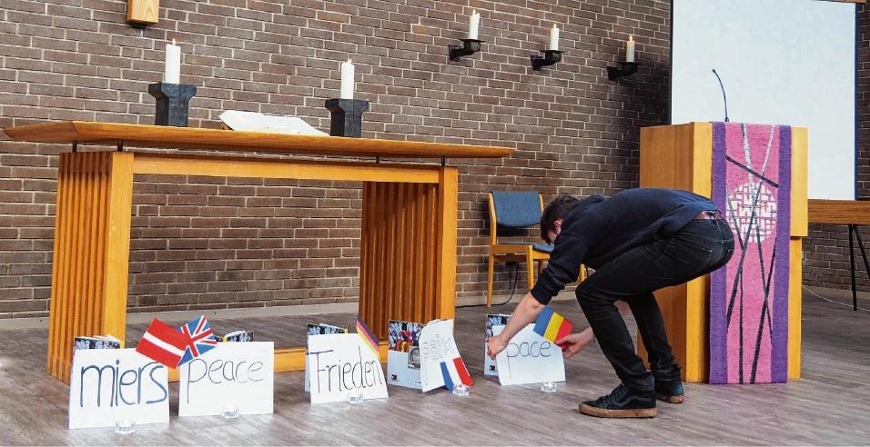 """Schüler der Ida-Ehre-Schule stellten Schilder mit der Aufschrift """"Frieden"""" in mehreren Sprachen in der Auferstehungskapelle auf."""