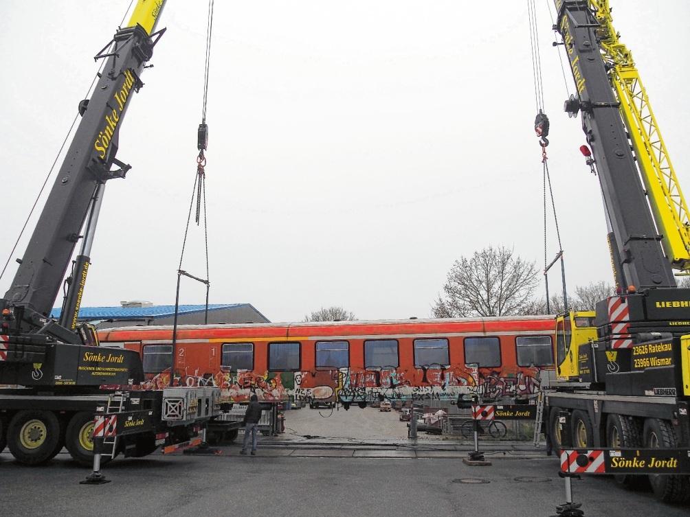 Ein spektakulärer Anblick: Zwei Schwerlastkräne hieven den Eisenbahnwaggon langsam auf zwei spezielle Drehgestelle. Rohde