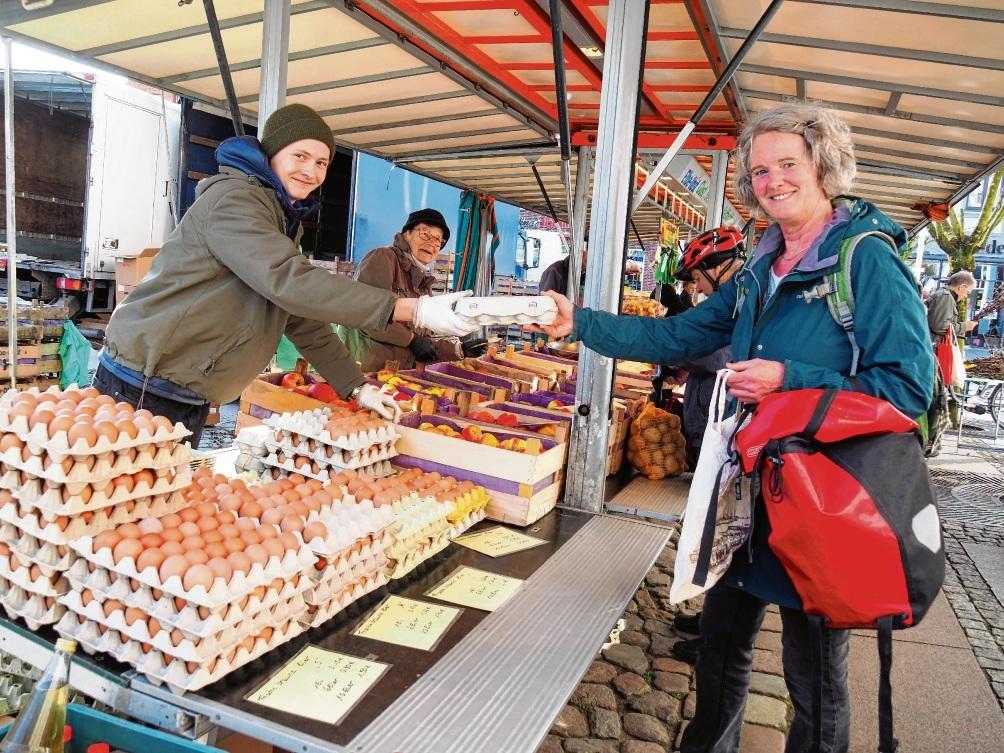 Astrid Lobreyer lässt sich am Obststand Nagel von Fausto Klenner zehn Eier reichen - mit Abstand!