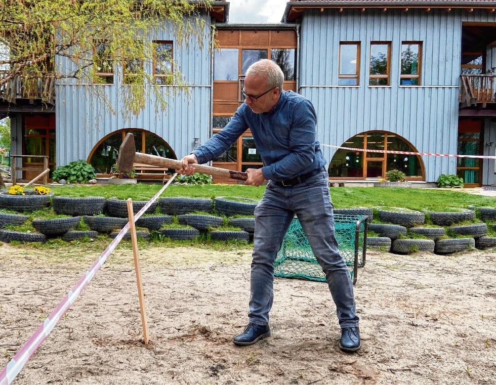 Mit schwerem Werkzeug hantiert Jens Reimann, um den Außenbereich der Kindertagesstätte  zu unterteilen. Seit Montag herrscht hier an der Sehmsdorfer Straße wieder reger Betrieb. ssi