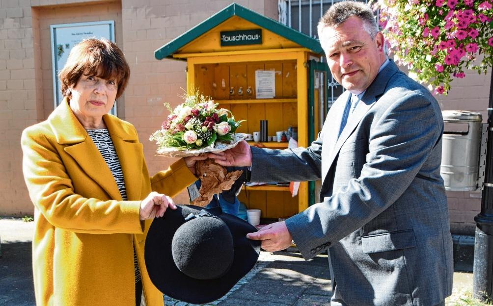 Karin Hoffmann überreicht den Hut für Tauschhaus und Bücherzelle an Bürgermeister Jörg Lembke. Link