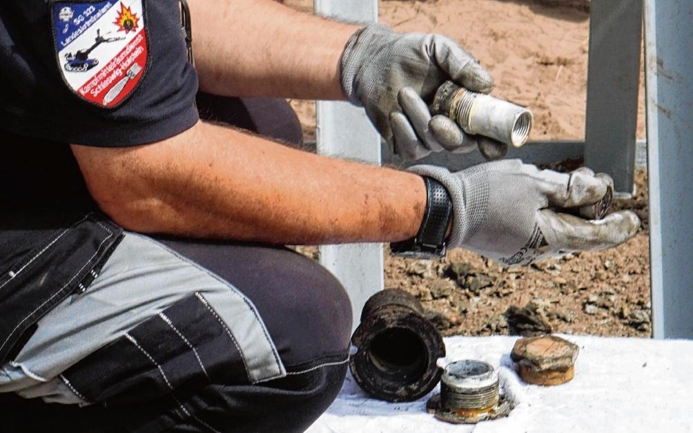 Ein Mitarbeiter des Kampfmittelräumdienst untersucht in Bad Oldesloe eine entschärfte Zündvorrichtung.  Patrick Niemeier