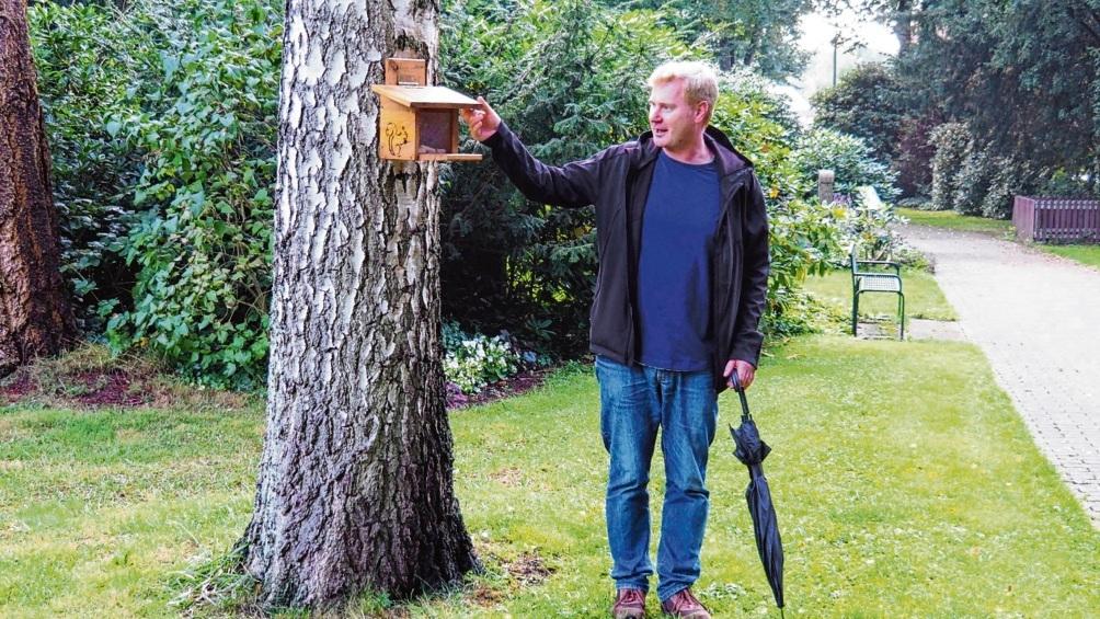Friedhofsleiter Jörg Lelke präsentiert eines von mehreren Futterhäuschen für Eichhörnchen.