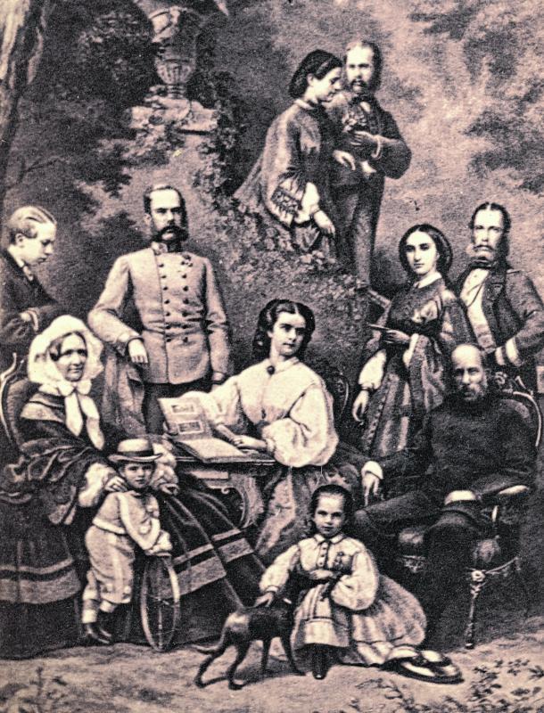 """Elisabeth von Österreich-Ungarn mit Fotoalbum umgeben von ihrer Familie um 1863. """"Sisi"""" sammelte begeistert Fotos. 18 ihrer Alben sind nun in einer Ausstellung zu sehen."""