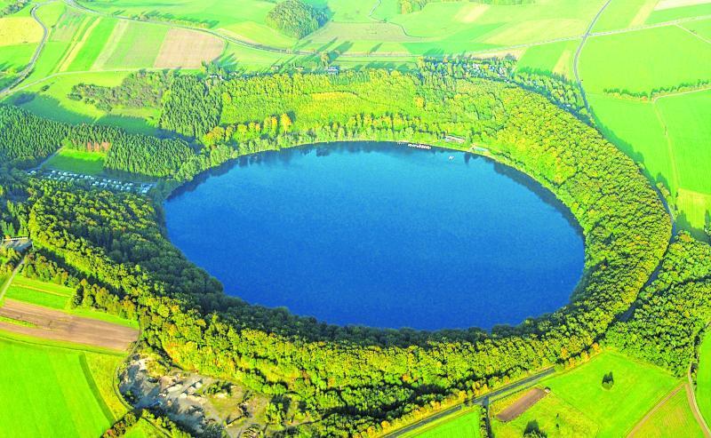 Hier siehst du das Pulvermaar in der Eifel. Maare sind Vertiefungen in der Erde, die wie Trichter aussehen. Sie entstanden bei Vulkanausbrüchen.
