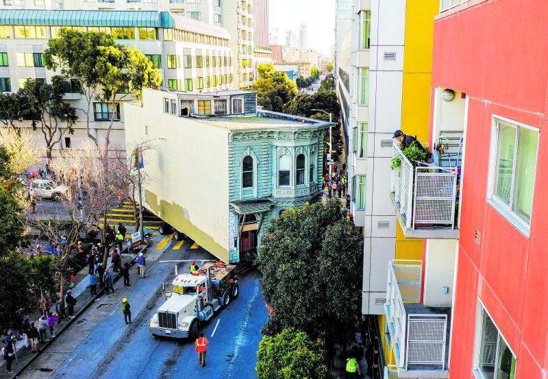 Ein Lastwagen zieht ein Haus durch die Stadt San Francisco im Land USA. Besser umziehen als abreißen, dachte sich der Besitzer.