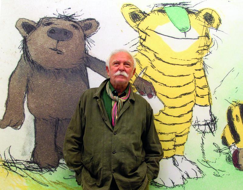 Janosch und seine beiden wohl wichtigsten Erfindungen: Der Autor posiert vor einem Bild, auf dem der kleine Bär und der kleine Tiger zu sehen sind.