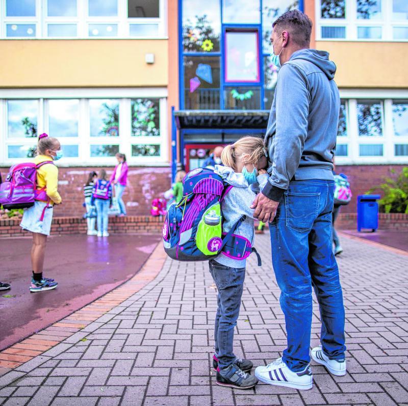 Schulanfängerin Lise wartet mit ihrem Papa vor der Schule auf den Unterrichtsbeginn am ersten Schultag. Manche Kinder gehen nicht so gerne zur Schule. In schlimmen Fällen nennt man das Schulangst.