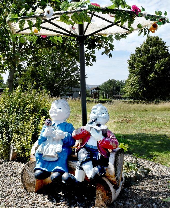 Dieses ältere Ehepaar hat es sich im Kleingartenverein Behrendorfer Wiesen gemütlich gemacht. Entspannt sitzen die beiden Figuren auf einer kleinen Holzbank unter einem Sonnenschirm.